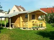Luka 300x350 s bočním přístřeškem - Zahradní domek Luka s čelním přesahem střechy 170 cm a terasou. Navíc je vybaven bočním přístřeškem. Je osazen okapy a svody, lemy střechy jsou oplechovány.