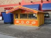 stánek 400x300 cm - Srubový stánek s čelním přesahem střechy 100 cm. Navíc je osazen prosklenou vitrínou a prodejním oknem. Atypické provedení dle přání zákazníka.