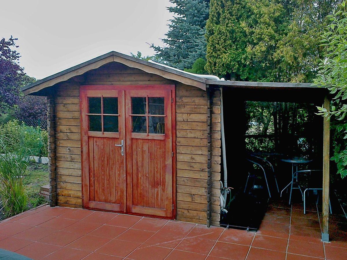Nářaďový domek Albert EKO DD s přístřeškem - Nářaďový zahradní domek Albert EKO s čelním přesahem střechy 30 cm a dvoukřídlými dveřmi a bočním přístřeškem. Standardní provedení.