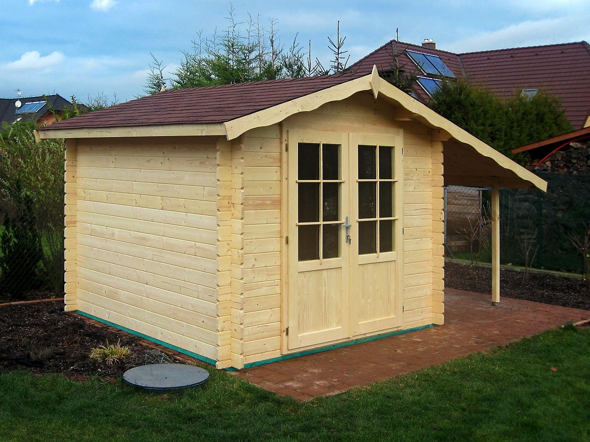 Nářaďový domek Albert EKO DD s přístřeškem - Nářaďový zahradní domek Albert EKO s čelním přesahem střechy 30 cm a dvoukřídlými dveřmi a bočním přístřeškem.